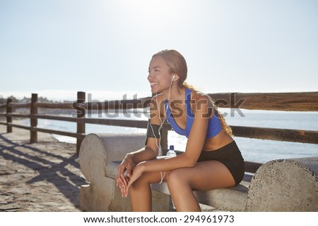 Young female jogger resting on the coastline while listening to music and smiling