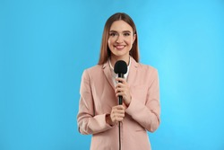 Young female journalist with microphone on blue background