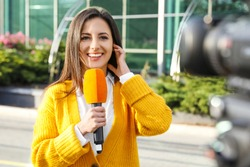 Young female journalist with microphone working on city street