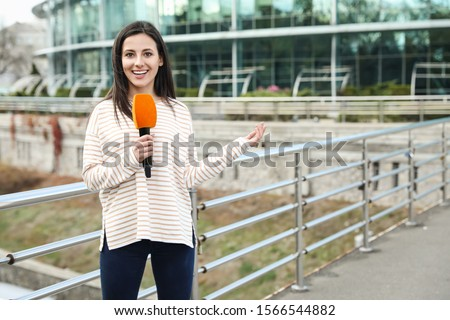 Young female journalist with microphone working on city street. Space for text Foto stock ©