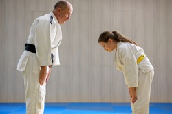Young female judo girl showing respect to old judo teacher