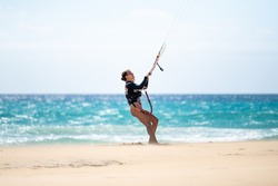 Young female kitesurfer on the beach looking at her kite. Sotavento beach in Fuerteventura