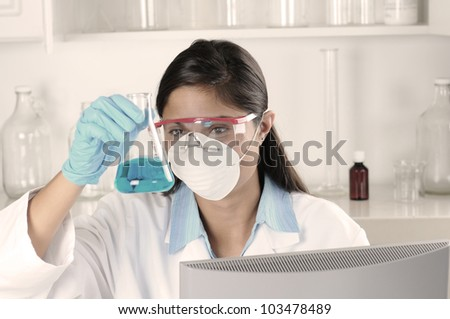 Young female lab tech seated behind computer monitor holding flask and inspecting contents. Horizontal format.