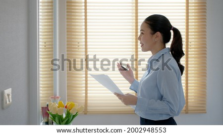 Young female leader, asia people lady or mba student happy standing smile look at in front of mirror pep talk for sale pitch hold paper document script public speak skill for job career self improve. Сток-фото ©
