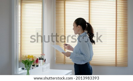 Young female leader, asia people lady or mba student happy standing smile look at in front of mirror pep talk for sale pitch hold paper document script public speak skill for job career self improve. Foto stock ©