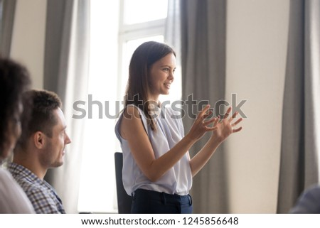 Young female leader, businesswoman, coach holding company briefing, talk to colleagues, training interns at company meeting, discuss business strategy, planning, brainstorming, team building, close up