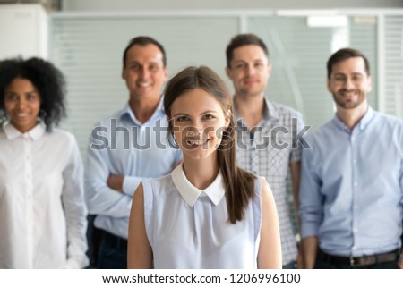 Young female leader, company employee or office worker smiling looking at camera, happy successful millennial professional manager business coach posing with diverse team staff members, portrait #1206996100
