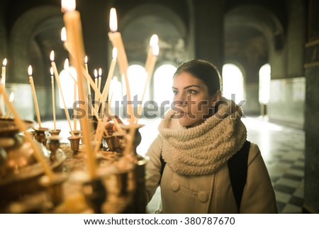 Young female lighting candles in a church during praying.Yellow votive candles burning.Woman praying to god at St. Alexander Nevsky Cathedral.Christianity.Strong christian religion faith