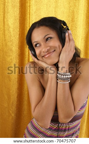 young female listens to her favorite song on her earphones. - stock photo