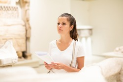 Young female local tourist reading guidebook with exhibition program looking at sculptures in historical museum