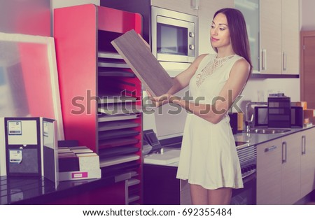 Young female looking material for facades for kitchen furniture