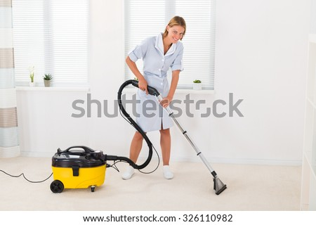 Young Female Maid In Uniform Vacuuming Floor