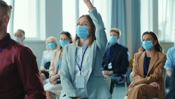 Young female manager raising hand on presentation asking a question. Business seminar. Conference meeting room. Diverse employees in face masks. Social distance. Quarantine.