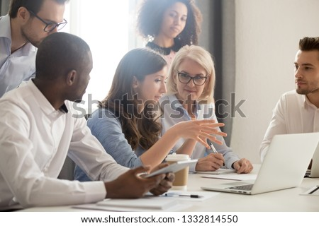Young female mentor leader coach teaching employees group analyzing online project explaining business strategy speaking training diverse corporate team with laptop using computer at office meeting