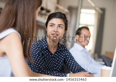 Young female multiracial workers sit at office desk talking discussing project, millennial women colleagues speak working together on computer, collaborating or cooperating in coworking space