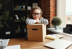 Young female newcomer in glasses and casual clothes smiling at camera while sitting at wooden table and leaning on carton box in dark modern office