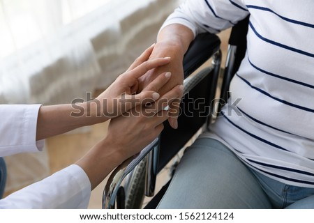 Young female nurse caregiver hold hand support disabled handicapped senior adult grandma patient sit on wheelchair, old paralyzed people with disability medical help assistance concept, close up view