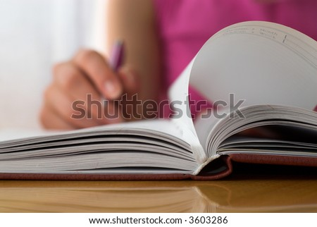 Young female opens notebook and planning her schedule.