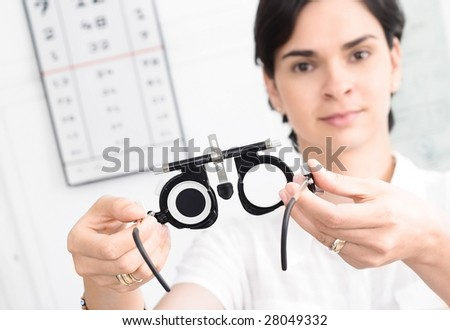 Young female optometrist with an universal messbrille in hand.