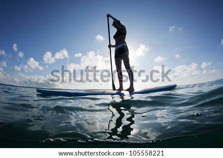 young female paddles a paddleboard off a Bahamian island Stockfoto ©