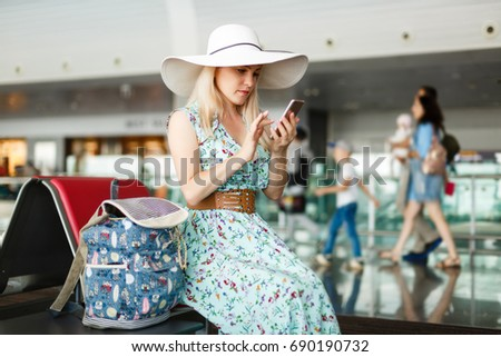 Young female passenger at the airport, using her phone while waiting for her flight, using travel app