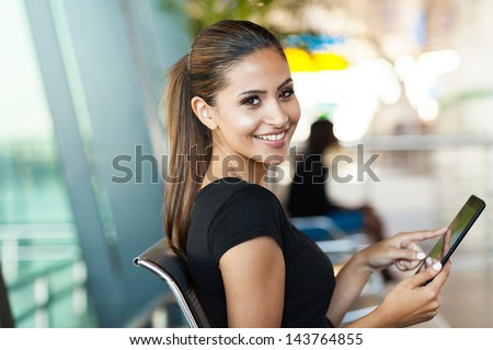 Young Female Passenger At The Airport Using Her Tablet Computer While Waiting For Flight
