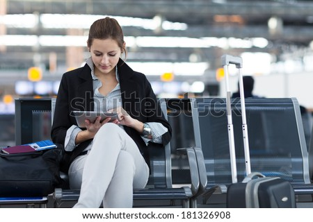 Young female passenger at the airport, using her tablet computer while waiting for her flight #181326908