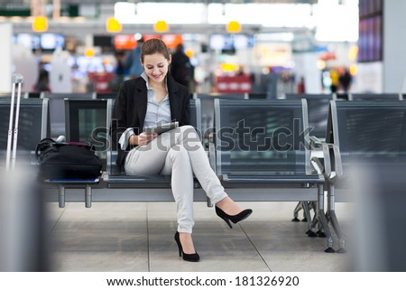 Young female passenger at the airport using her tablet computer while waiting for her flight