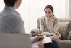 Young female patient talking with her therapist in the office, mental health and psychotherapy concept
