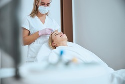 Young female patient undergoing the platelet-rich plasma therapy for hair loss in a beauty clinic