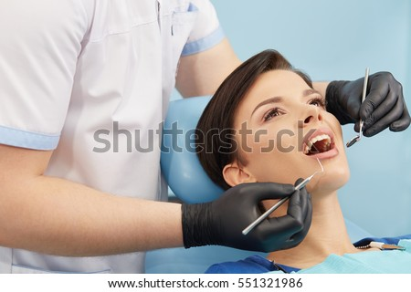 Young female patient visiting dentist office.Beautiful woman with healthy straight white teeth sitting at dental chair with open mouth during a dental procedure.Dental clinic.Stomatology.Dental caries