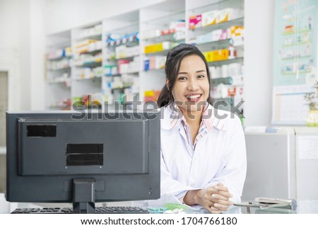 Young female pharmacist working on computer  in drugstore