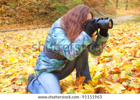 Young female photographer in autumn forest at work