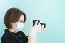 young female photographer in medical mask and white medical gloves holds her camera on light blue backgrouund, protection from viruses and coronavirus pandemic, health care concept