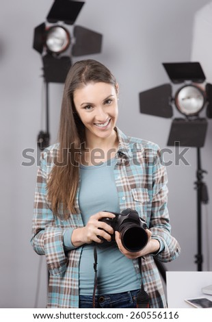 Young female photographer posing in her professional studio, holding a digital camera with lighting equipment on background