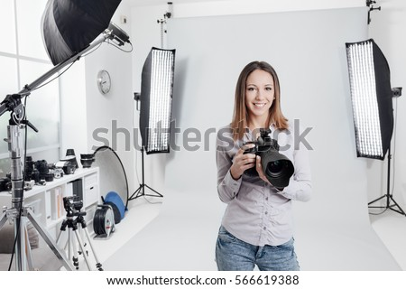 Young female photographer posing in the photo studio, she is smiling and holding a professional digital camera #566619388