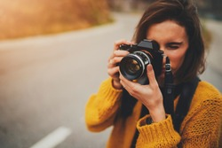 Young female photographer taking photograph on vintage camera outdoors, blank space for text message or design, tourist girl enjoying road trip in Europe, flare light