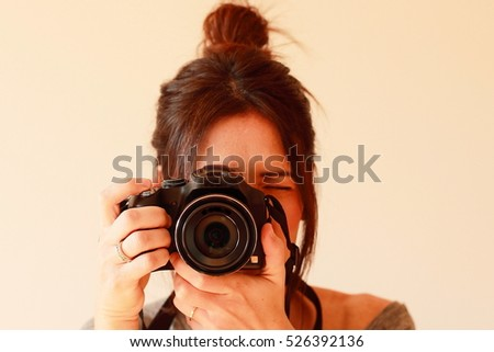 Young female photographer with camera on soft background taking a picture with her new camera