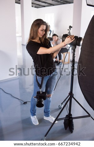 Young female photographer work in studio. Beautiful woman with camera is setting photographing equipment in studio getting ready for a photo shoot - Shutterstock ID 667234942