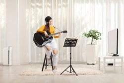 Young female playing an acoustic guitar with headphones and sitting on a chair at home in a living room