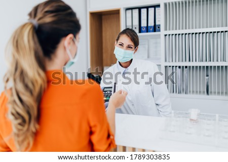 Young female practitioner or nurse with face protective mask working at clinic reception desk. She is helping to patient to make contactless payment for medical services. Photo stock ©