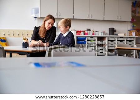 Young female primary school teacher and schoolboy sitting at a table working one on one, selective focus