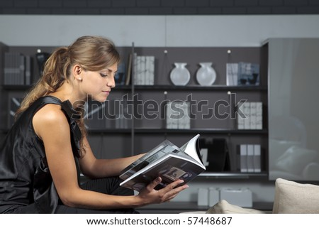 Young female reading a magazine in the living-room