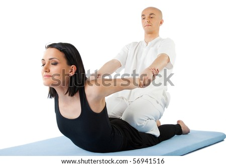 Young female receiving massage by therapist in traditional thai position - stock photo