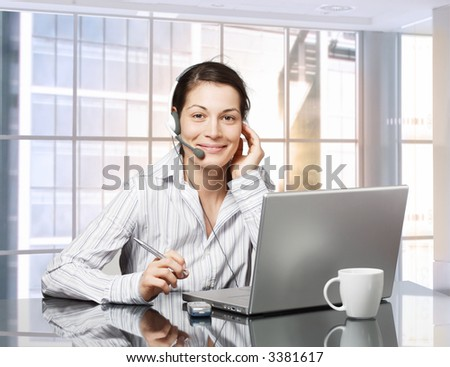Young female receptionist works on laptop computer in brightly lit office. Daylight, indoor, office.