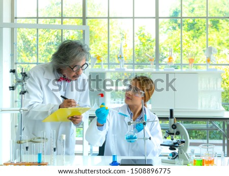 Young female research scientist and Senior male professor researchers working in life scientific laboratory.