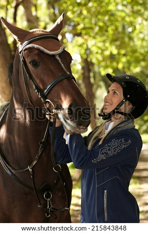 Young female rider looking at horse with love, outdoor photo.
