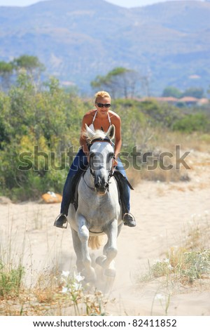 Young female rider on the beach