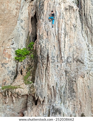 Young female rock climber, concept for overcoming obstacles.