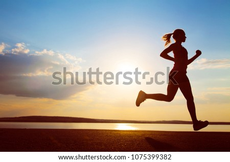 Young Female runner silhouette against the sunset #1075399382